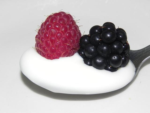 Yogurt senza lattosio bianco, in un cucchiaio con mora e lamponi